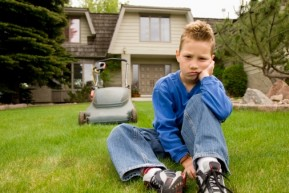 Image of young boy sitting on lawn with a lawn mower behind him to represent lawn mower injuries to children.