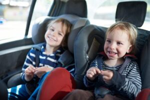 two kids laughing in their car seats