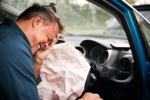 man in pain after being injured by airbag